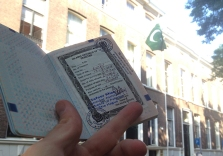 An Unexpected Experience Having learned from my wonderful experience of applying for an Indian Visa, I came prepared when applying for the Pakistani visa. Beside the required documents; copies of Hotel bookings, motorcycledocuments, Carnet de Passage, Travel Insurance and much more. I arrived early in the morning at the Embassy around 9.30. Once inside I was still the only one applying for a visa, thus it took about 5 minutes until I could hand over my papers. They red everything very thoroughly and asked additional question concerning my trip and places of visit. Since I wrote everything down (and had a visual travelplan) in my introductionletter; these answers where easily verified. The hotelbooking added to this story even though they did not require the copies immediately. I was asked to sit down as the documents would be prepared for judgement. Once seating I felt the need to add more clarity in my story, so I grabbed the additional papers walked over to the reception and handed over a copy of my Carnet the Passage and motorcycledocuments. Then I noticed they were already busy sticking a document in my passport with glue that reeked of instant death. With a well hidden smile and a lot of relief I made my way back to my seat. With a few minutes later paying for my visa and having some small talk about the trip, the passport was handed back to me with a sincere ''safe travels'' wish. And so this picture was made outside the Embassy of Pakistan, 25 minutes after I had applied for my Visa.