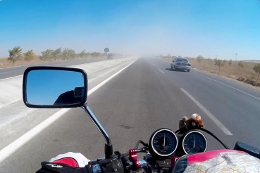 Facing a miniature sandstorm on the road. Better get used to it, there will be more of those along the way.